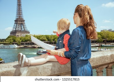 Seen from behind trendy mother and daughter tourists near the parapet on the embankment of the river Seine overlooking Eiffel tower in Paris, France holding map and pointing.