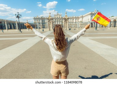Seen from behind trendy woman with Spain flag rejoicing against Royal Palace