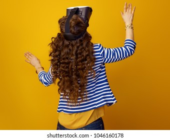 Seen from behind trendy woman in striped jacket on yellow background using VR headset