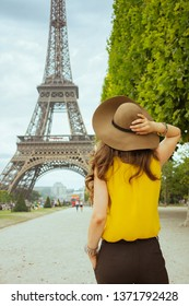Seen from behind trendy woman in yellow blouse and hat in the front of Eiffel tower in Paris, France having excursion.