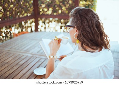 Seen from behind woman in white shirt with eyeglasses sitting at the table drinking coffee and reading book in the terrace.
