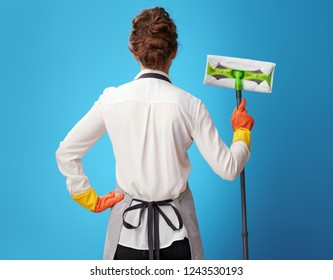 Seen from behind young cleaning lady in apron with mop isolated on blue background. Efficient, tidy, reliable and polite - the main characteristics of professional cleaning service workers