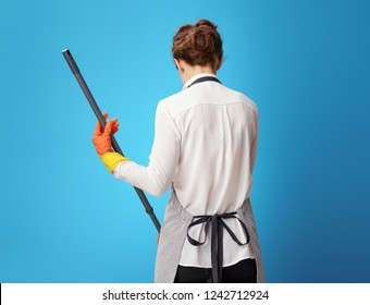 Seen from behind young housemaid in apron using mop against blue background. Attention to detail and accuracy distinguishes a professional cleaner