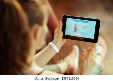 Seen from behind young sports woman in sport clothes in the modern house using home workout trainer app in tablet PC.