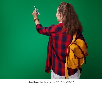 Seen from behind young student woman in a red shirt with backpack and headphones writing in the air with a big pen on green background