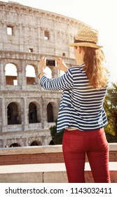 Seen from behind young tourist woman in a striped jacket in Rome, Italy taking photo with smartphone