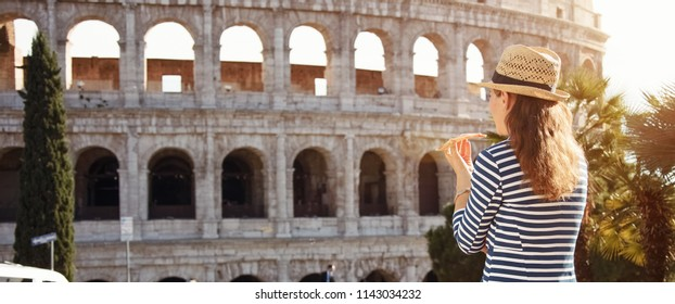 Seen from behind young tourist woman in a striped jacket in the front of Colosseum eating pizza