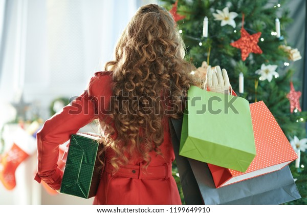 Seen from behind young woman in red trench coat with shopping bags and Christmas present box near Christmas tree