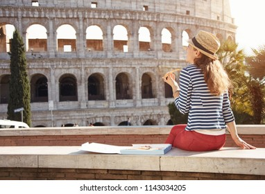 Seen from behind young woman in a striped jacket in the front of Colosseum eating pizza
