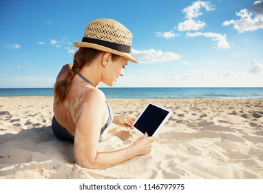 Seen from behind young woman in swimwear on the beach using tablet PC