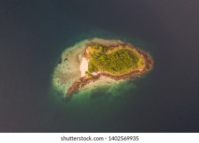 Seen from a bird's eye view, an idyllic island is surrounded by a healthy coral reef in Komodo National Park, Indonesia. This tropical area is known for its marine biodiversity as well as its dragons.