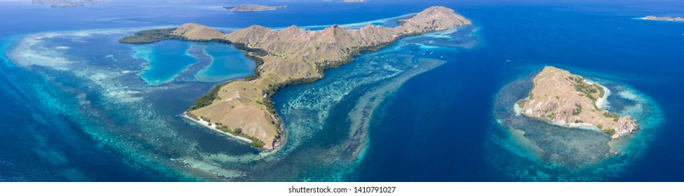 Seen from a bird's eye view, idyllic islands are surrounded by healthy coral reefs in Komodo National Park, Indonesia. This tropical area is known for its marine biodiversity as well as its dragons.