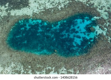 Seen from a bird's eye view, a shallow blue hole is surrounded by a coral reef in Komodo National Park, Indonesia. This tropical area is known for its marine biodiversity as well as its dragons.