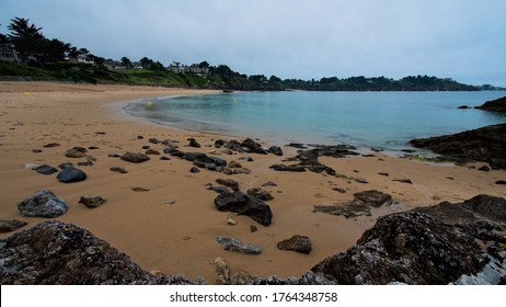 Seen on a bay, its houses on the cliff, its sandy beach from rocks above the beach and under a cloudy sky