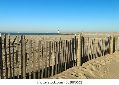 SEEN ON THE LIGHTHOUSE BEHIND  WOODEN BARRIER ON THE BEACH OF CALAIS IN WINTER , PAS DE CALAIS, FRANCE