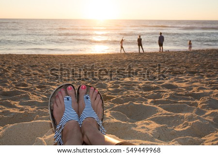 ca58d95cd1aecb Seen sea from the beach with the feet of a woman in foreground and a family