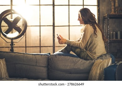 Seen from the side,a brunette woman is smiling, looking down at her phone sitting on the back of a sofa. Industrial chic ambiance and cozy atmosphere, sunlight is streaming through the loft window.