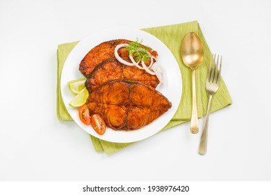 Seer fish fry arranged beautifully and garnished with onion, lemon and tomato slices on white ceramic plate placed on green napkin with white textured background.
