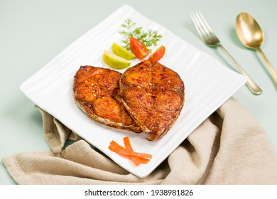 Seer fish fry arranged beautifully and garnished with onion, lemon and tomato slices on white square shape ceramic plate placed on grey colour napkin with ice  blue textured background.