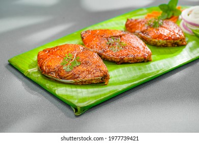 Seer fish fry arranged beautifully and garnished with onion, lemon and tomato slices on banana leaf covered base which is placed on solid green texture with abstract shadows on background.