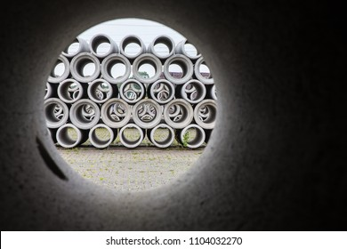 See-through with pile of concrete sewer pipes at concrete plant