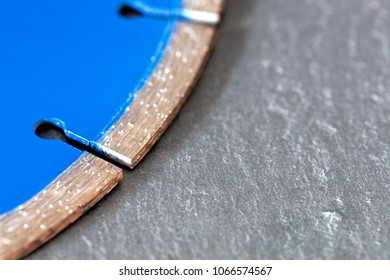 Segment of a diamond blue cutting disc on a background of gray concrete close-up.