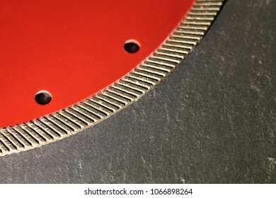 Segment of a diamond red disc for cutting against a gray granite background close-up.