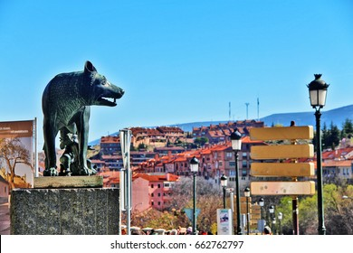 Segovia, Spain - March 16, 2017 - Loba Capitolina (Capitoline Wolf), sculpture of she-wolf breastfed to twins, Romulus and Remus, founder of Rome, at foot of Roman Aqueduct in Plaza del Azoguejo