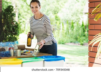 Segregating waste to correct containers, a daily routine of smiling young woman