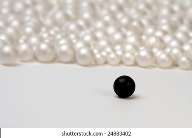 Segregation concept shot with a single black ball and group of white ones
