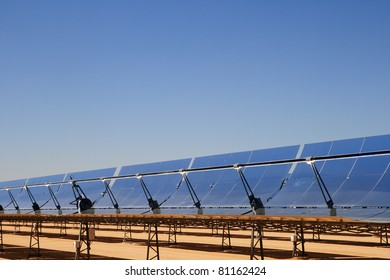 SEGS solar thermal energy electricity plant with parabolic mirror solar collectors concentrating the sunlight and blue sky copy space