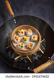 Sei Hei Gau (vier Jahreszeiten) Dumplings, die in einem Bambusdampfampfer über einer Wok-Pfanne dampfen.