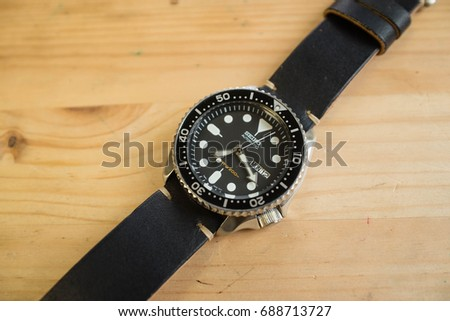 Seiko SKX007 Divers  watch with a leather strap on a wooden background 18e7b14090c6