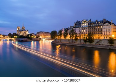 The Seine in Paris, France at Night with the Notre Dame Cathedral in the Distance