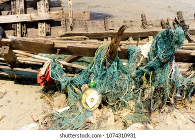 Seines or trawls or fishnets stuck on the old wooden keel of shipwreck that lay on the tropical beach