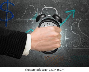 Seizing the time and present opportunities concept. Businessman hand grasping alarm clock, with dark doodles concrete wall background.