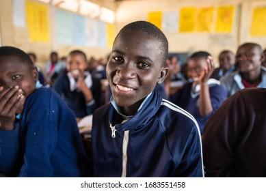 Sekenani / Kenya - September 20, 2016: Portrait of Maasai schoolboy smiling while hi classmates laugh in a full classrom of a school in West Kenya