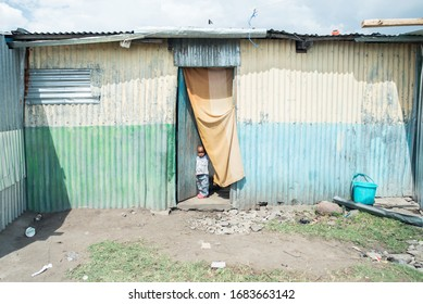 Sekenani / Kenya - September 20, 2016: Little Afrikan boy opens curtain at the door of his basic poor house during a sunny day