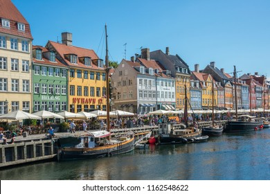 Selandia, Denmark - august 04, 2018: View of the Nyhavn canal, with old sailing ships moored in their docks and colorful houses in the background, in the historic center of the city of Copenhagen