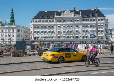 Selandia, Denmark - august 04, 2018: Traffic of people and vehicles in the square of Kongens Nytorv and the Angleterre hotel in the background, in the historical center of the city of Copenhagen