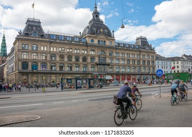 Selandia, Denmark - august 04, 2018: Group of cyclists circulating in front of the Magasin du Nord department store in the historic center of the city of Copenhagen