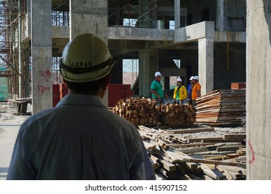 SELANGOR - APRIL 30: Builder On Building Site Looking At Plans With Apprentices at Selangor, Malaysia on April 29, 2016.