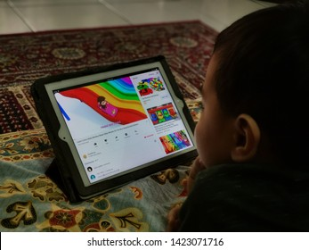 Selangor, Malaysia - 12 JUNE 2019 : Learning colors through nursery rhymes on youtube channel being watched by a cute toddler at home from ipad.