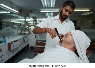 Selangor, Malaysia - 22ND JUNE 2019; An Indian hairdresser cutting mustache of male client. Hairstylist serving client at barber shop.