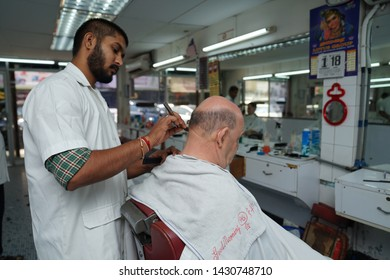Selangor, Malaysia - 22ND JUNE 2019; An Indian hairdresser shaving hair of male client. Hairstylist serving client at barber shop.