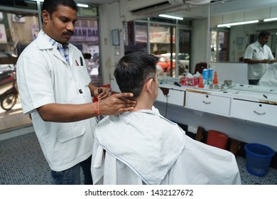 Selangor, Malaysia - 22ND JUNE 2019; An Indian barber cutting hair of male client. Hairstylist serving client at barber shop.