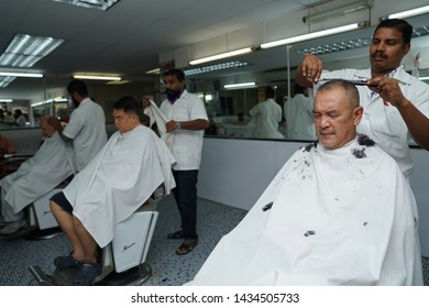 Selangor, Malaysia - 22ND JUNE 2019; An Indian barber cutting hair of male client. Hairstylist serving customer at barber shop.