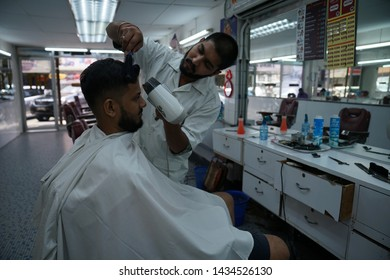 Selangor, Malaysia - 22ND JUNE 2019; An Indian barber dry hair of male client using hair dryer. Hairstylist serving customer at the barbershop.