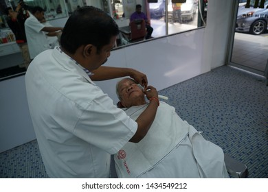 Selangor, Malaysia - 22ND JUNE 2019; An Indian barber shaving beard of male client using sharp razor. Hairstylist serving customer at the barbershop.