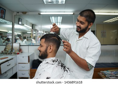 Selangor, Malaysia - 22ND JUNE 2019; An Indian barber cutting hair of male client using sharp scissors. Hairstylist serving customer at the barbershop.
